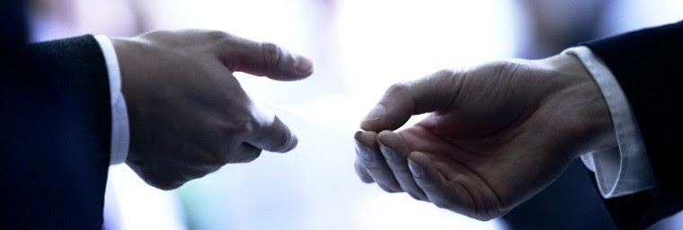Visitkort til virksomheder vist med hænder